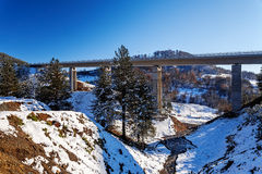 Mountain bridge in winter with snow and blue sky Royalty Free Stock Photography