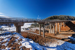 Mountain bridge in winter with snow and blue sky royalty free stock image