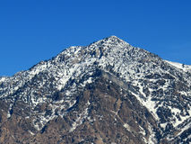 Mountain Bulge. Face of mountain that bulges with a ridge or craggy peak in winter snow stock image