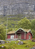 Mountain cabin. Red cabin with turf roof against a steep mountain cliff Royalty Free Stock Photos