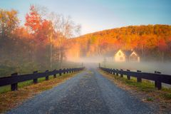Mountain Cabin in Fog. A fence lined lane leads into the fog with colorful foliage and blue skies in the background stock photography