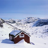 Mountain cabin in snowy landscape Royalty Free Stock Images