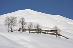 Mountain cabin snowy landscape. Mountain panorama of the snow in a sunny winter day Royalty Free Stock Photos