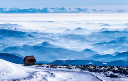 Mountain cabin with the winter view. Mountain cabin with the view on mountain ranges under the snow, fog and clouds, mountain Kopaonik, Serbia Stock Photo
