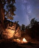 Mountain campsite at night amid huge steep rock formation. Tourist tent lit by burning campfire. Fantastic landscape at summer night. Brightly burning small stock images