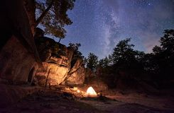 Mountain campsite at night amid huge steep rock formation. Tourist tent lit by burning campfire. Fantastic landscape at summer night. Brightly burning small royalty free stock image