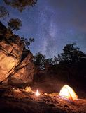 Mountain campsite at night amid huge steep rock formation. Tourist tent lit by burning campfire. Mountain campsite at summer evening amid huge steep rock royalty free stock photo