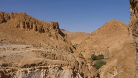 Mountain canyon in Oasis Chebika nearby Atlas Mountains in Sahara desert. Tourist people traveling in national park in Tozeur, Tunisia stock video footage