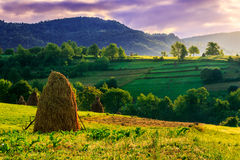 Mountain cascade. Stack of hay on the hillside under a menacing sky in the early morning Royalty Free Stock Photos