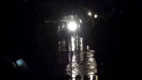 Mountain Cave with icicles underground mine in which miners move in helmets with flashlights stock video