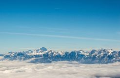Mountain chain above the clouds. Mountain chain covered in snow above the clouds Stock Photo