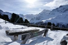 Mountain chalet, wood bench. Val Venosta, Dolomites: wood bench in a snow panorama and sun in the sky Stock Image