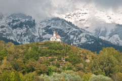 Mountain-chapel. Chapel on the top of a hill, between Kufstein and Innsbruck, inn valley, austria, with snowcovered mountainrange in the background Stock Photo