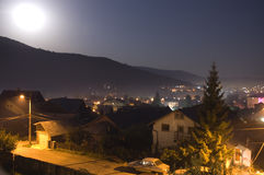 Mountain city. Busteni city by night with Bucegi mountains and moon in background Stock Photography