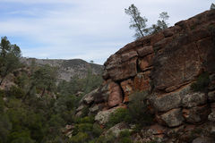 Mountain Cliff Landscape. A panoramic outdoor vista view of a rugged western landscape and canyon with the surrounding mountains along a trail in Pinnacles Stock Images