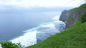 Mountain cliff on ocean shore and water waves on skyline landscape. High cliff mountain covered tropical plants and. Trees on splashing sea waves background stock video footage