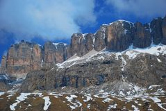 Contrasting Mountain Cliff in Passo di Sella, The. A snow-capped mountain cliff in the famous Passo di Sella mountain pass in the western Italian Dolomites Stock Photos