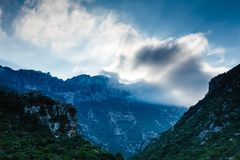 Mountain cliffs against sky with clouds Stock Photos
