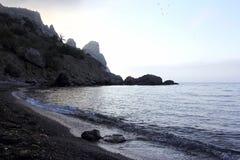 Mountain cliffs along the shoreline of the sea. The mountain cliffs along the shoreline of the sea Stock Image