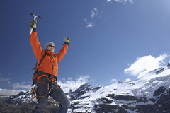 Mountain Climber With Arms Raised Against Snowy Mountains. Male mountain climber raising hands with arms raised against snowy mountains Stock Images