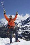 Mountain Climber With Arms Raised On Snowy Peak. Male mountain climber raising hands with icepick on top of snowy peak Stock Photography