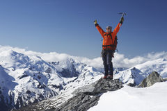 Mountain Climber With Arms Raised On Snowy Peak. Male mountain climber raising hands with icepick on top of snowy peak stock images