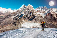 Mountain Climber ascending high Altitude Peak walking in Cosmic Terrain. Mountain Climber in high Altitude Clothing and Boots carrying heavy Backpack walking on Royalty Free Stock Photos