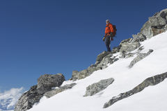 Mountain Climber Descending Snow And Boulder Slope. Low angle view of a male mountain climber descending snow and boulder slope Stock Photography