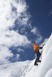 Mountain Climber Going Up Snowy Slope With Axes Royalty Free Stock Image