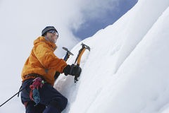 Mountain Climber Going Up Snowy Slope With Axes. Low angle view of a male mountain climber going up snowy slope with axes against clouds royalty free stock images