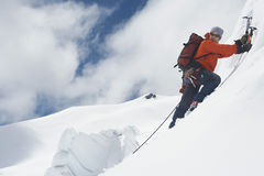 Mountain Climber Going Up Snowy Slope With Axes royalty free stock photo
