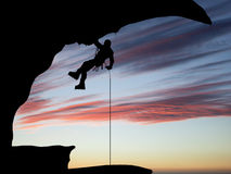 Mountain climber hanging on a rope on the background of sky Stock Image