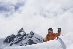 Mountain Climber Reaching Over Snowy Peak Stock Photo