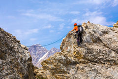 Mountain Climber on rocky ridge with rope and safety gear. Mountain Climber moving along sharp rocky Ridge using belaying Rope and safety Gear Stock Photo