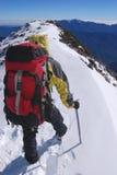 Mountain climber on snowy summit Stock Photo