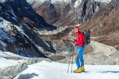 Mountain Climber using Cell Phone at high Altitude extreme Conditions Stock Photos