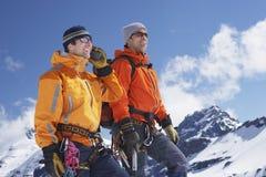 Mountain Climber Using Walkie Talkie By Friend On Snowy Peak. Two male mountain climbers on snowy peak against sky with one using walkie talkie stock photo