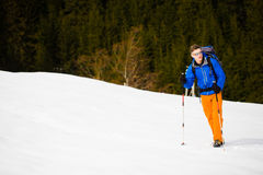 Mountain climber walks on a snowy slope. Royalty Free Stock Photography
