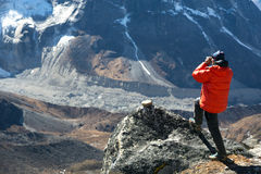 Mountain Climber in warm Jacket taking Picture of Valley. Mountain Climber in warm and red down Jacket taking Picture of Valley and Glacier on photo camera Royalty Free Stock Images