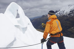 Mountain Climber With Compass By Ice Formation In Mountains Stock Photos