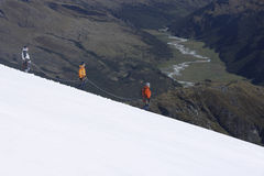 Mountain Climbers Descending Snowy Slope. Side view of three hikers descending at a distance on snowy mountains Royalty Free Stock Photography