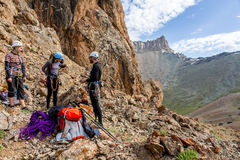 Mountain climbers discussing tactic of ascent. Three people male female talking each other about plan of climb and using gear staying on red rocky terrain high Stock Photography
