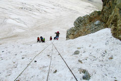 Mountain climbers with ropes on snow Stock Photography