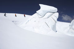 Mountain Climbers Walking Past Ice Formation. Side view of three hikers walking past ice formation at a distance in snowy mountains royalty free stock photo
