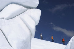 Mountain Climbers Walking Past Ice Formation. Side view of three hikers walking past ice formation at a distance in snowy mountains stock image