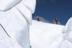 Mountain Climbers Walking Past Ice Formations Royalty Free Stock Image