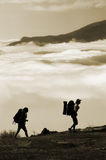 Mountain climbing. Two hikers with backpacks climbing a peak on cloud sky background Stock Image