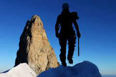 Mountain climbing. Silhouette of a mountaineer with rocky pinnacle in the background Stock Photography