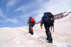 Mountain climbing. Two climbers are moving to the top of the glacier Stock Photos