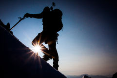 Mountain climbing. Silhouette of a climber on a steep slope at dawn Royalty Free Stock Photo